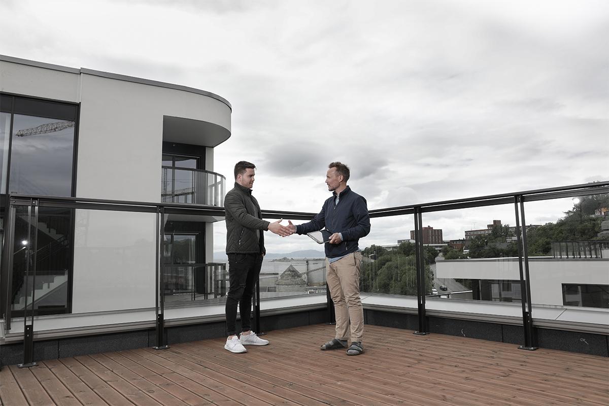 Raymond og Christian utveksler håndtrykk på toppen av leilighetsbygningen